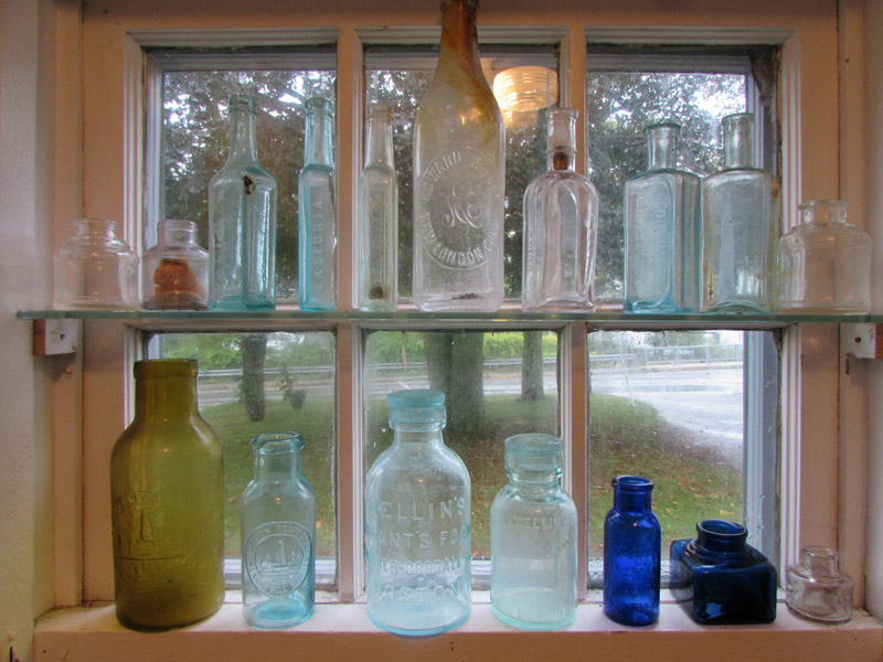 Bottles from 100 years ago on display at the Woods Hole Historical Museum that were collected by Becky Lash, who will tell about them October 11. (Photo by Robert Grosch)